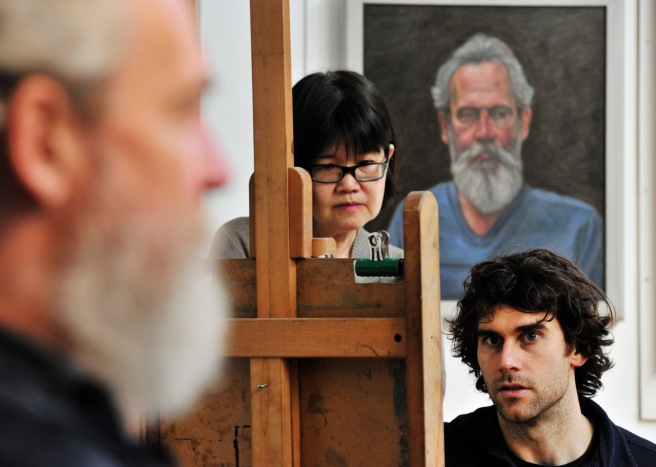 Artist at easel with model and student